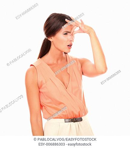 Lovely female with hand on head gesturing headache with closed eyes in white background