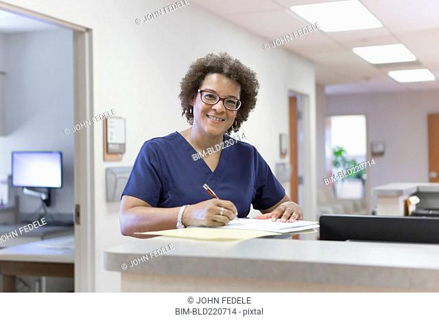 African American nurse writing in hospital