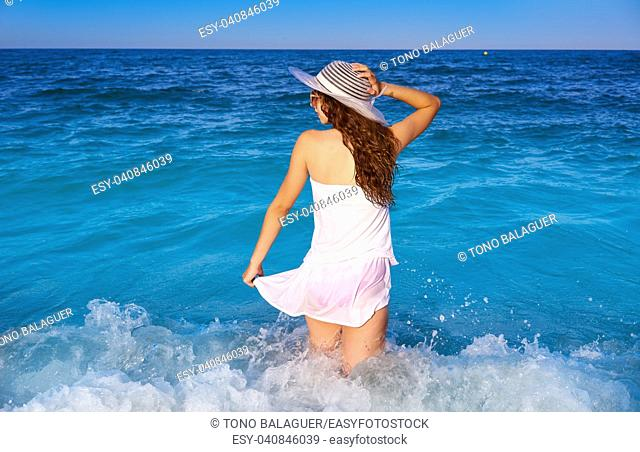 Girl in beach sea shore with waves splash and summer white dress