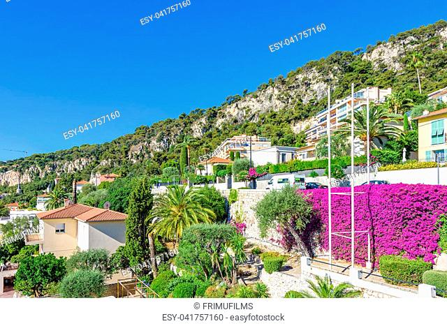 Beautiful daylight view to buildings, cars parked on road and green trees on mountains. Bright blue clear sky on background