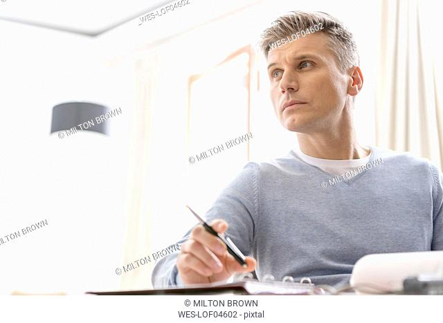 Man sitting at desk with folder and pen