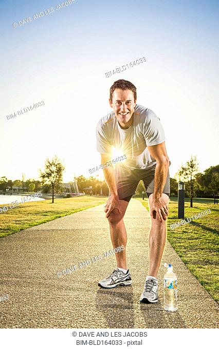 Caucasian runner resting on concrete path in park