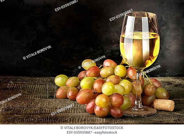 Glass of white wine with grapes on vintage wooden table