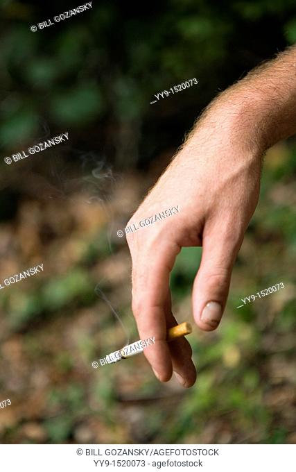 Close-up of hand with cigarette - Cedar Mountain, North Carolina, USA