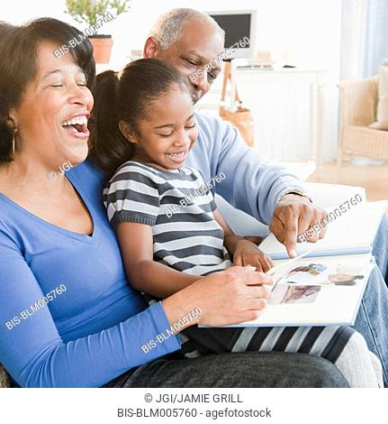 Black grandparents looking at photographs with granddaughter