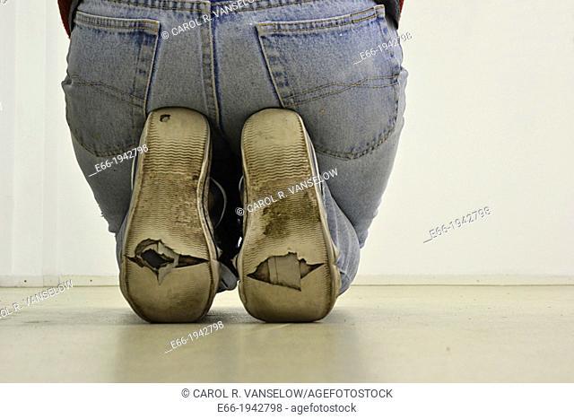 woman kneeling, sitting on feet, wearing worn out sneakers