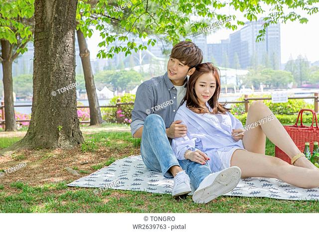 Young couple having picnic at park in spring