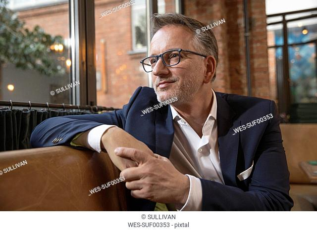 Portrait of content businessman waiting in a restaurant