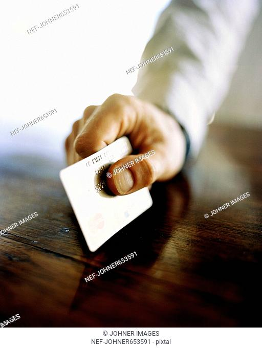 A hand holding a credit card