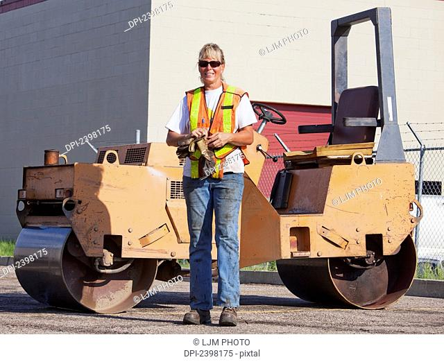 Female operator with a steam roller for repairing pot holes in a parking lot; Edmonton, Alberta, Canada