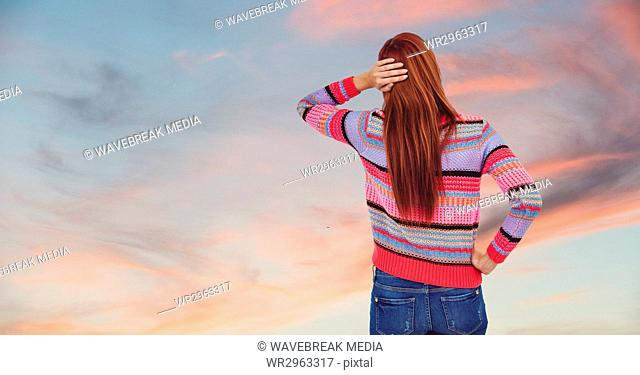 Rear view of redhead woman against sky