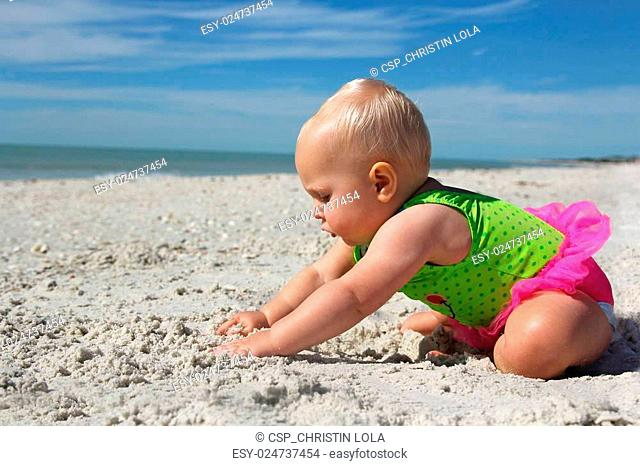 Cute Baby Girl Playing in the Sand at the Beach