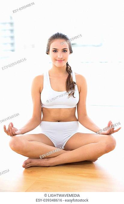 Smiling relaxed brunette meditating in bright room