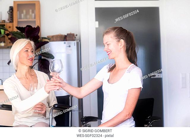 Mother in wheelchair with daughter giving her a wine glass