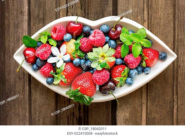 Mix of fresh berries on a white plate in shape of lips, on wooden background, top view