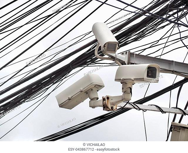 Old CCTV camera security hanging on chaos of cables and wire, Bangkok, Thailand