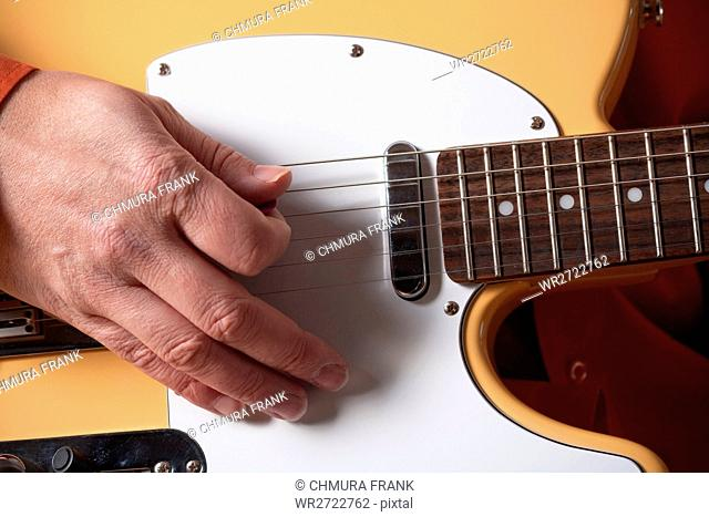 closeup of hands of a musician playing electric guitar