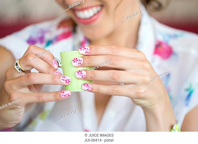 Close up of woman holding tiny cup with flower design on manicured fingernails