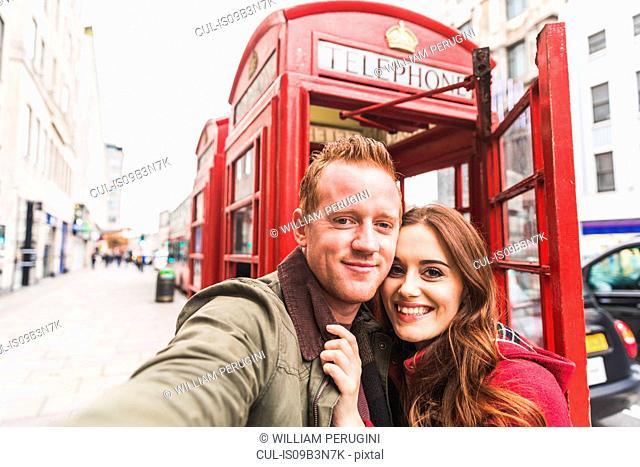 Couple taking selfie by telephone booth, London, UK