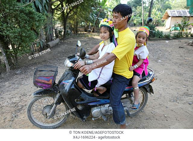 A father rides his moped with his two daughters in the Longneck village Approximately 300 Burmese refugees in Thailand are members of the indigenous group known...