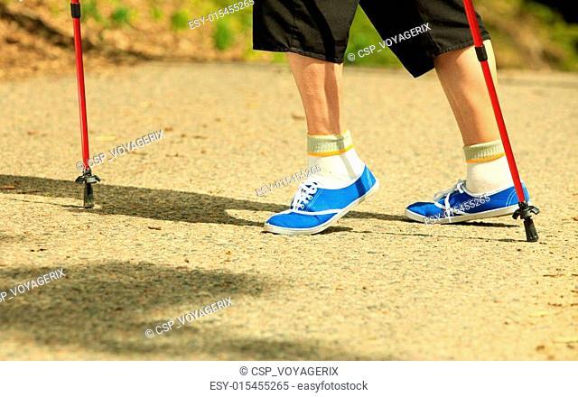 active senior legs in sneakers nordic walking in a park