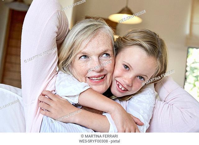 Portrait of smiling little girl hugging her grandmother