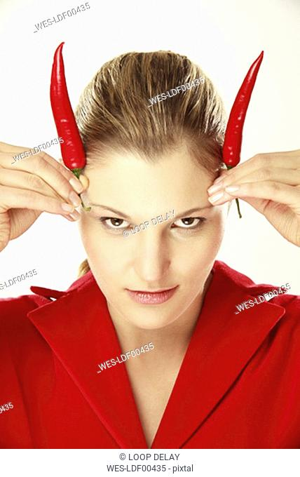Young woman using chilis as horns