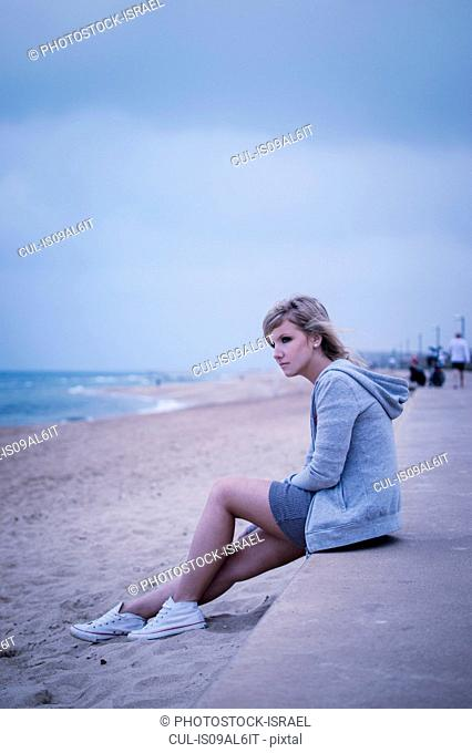 Young woman sitting on sea wall, looking out to sea