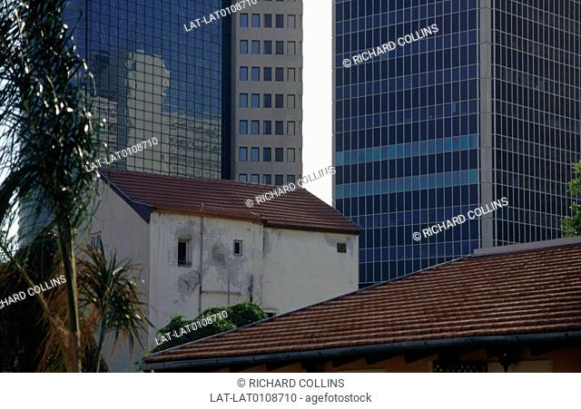 New contrasted with old. Small old bulding with new modern high rise glass buildings. Shabazi district