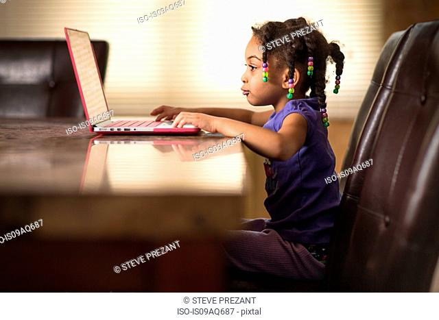 Cute girl at dining table using laptop