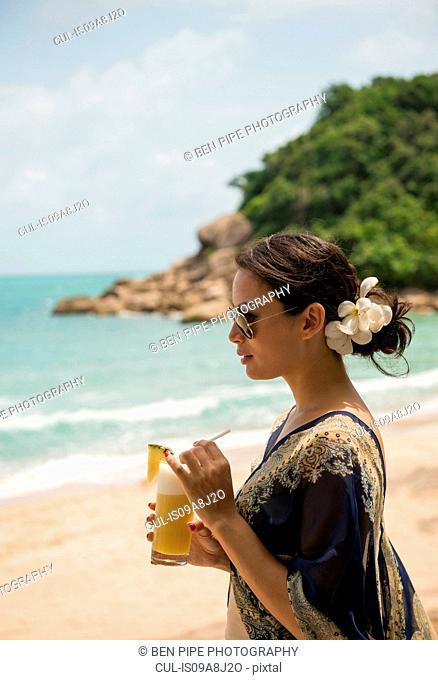 Woman with drink on beach, Banyon Tree Resort, Ko Samui, Thailand