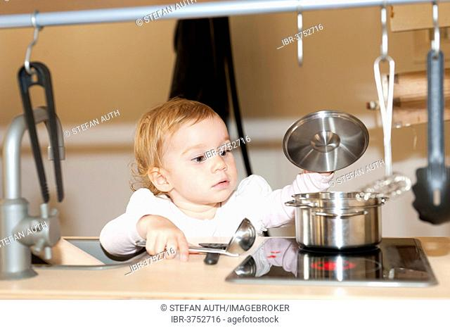 Little girl playing in a children's kitchen, looking into a pot, Germany