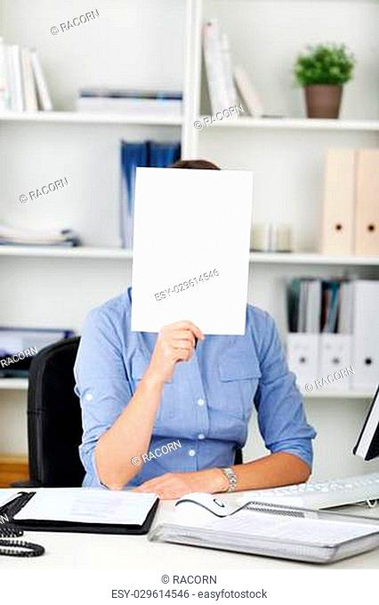 Businesswoman holding a blank white sign with copyspace for your advert or text in front of her face as she sits at her desk in the office