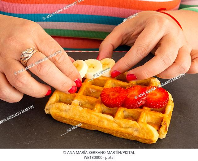 A woman with red fingernails placing strawberry and banana pieces on a Belgian waffle