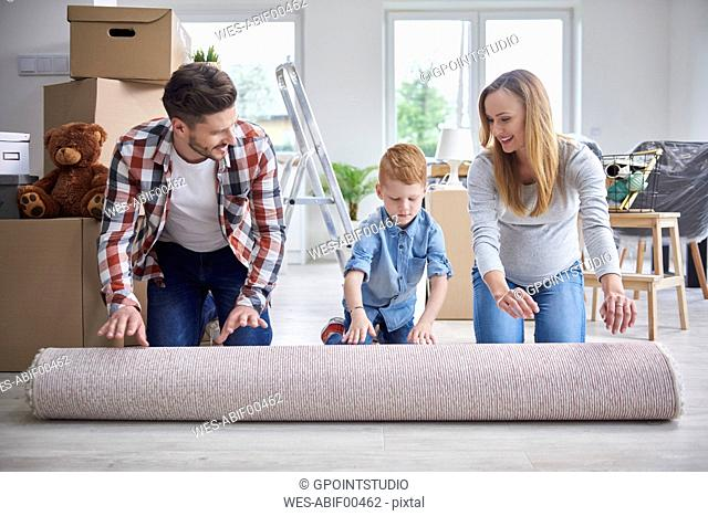 Family unrolling a carpet in new flat