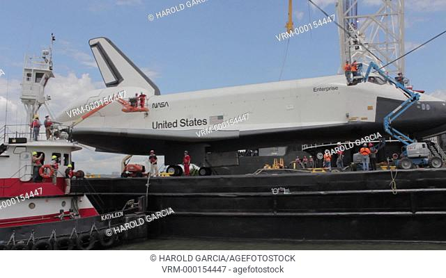 Men preparing The Space Shuttle Enterprise to be transferred to the USS Intrepid Aircraft Carrier to be put on permanent display at Sea and Space Museum on the...