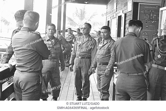 American soldiers and South Vietnamese soldiers standing together on the porch of a building at a military base, map with Vietnamese writing and palm trees...