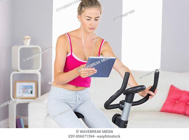 Sporty focused blonde training on exercise bike using tablet