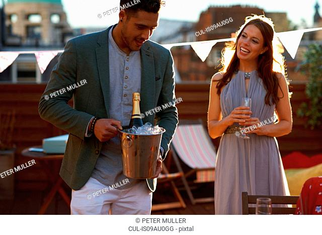 Mid adult couple at party on roof terrace holding ice bucket with champagne smiling