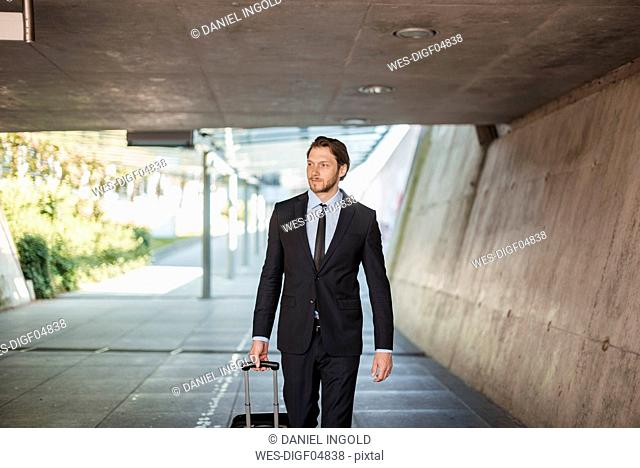 Businessman with rolling suitcase walking in underpass