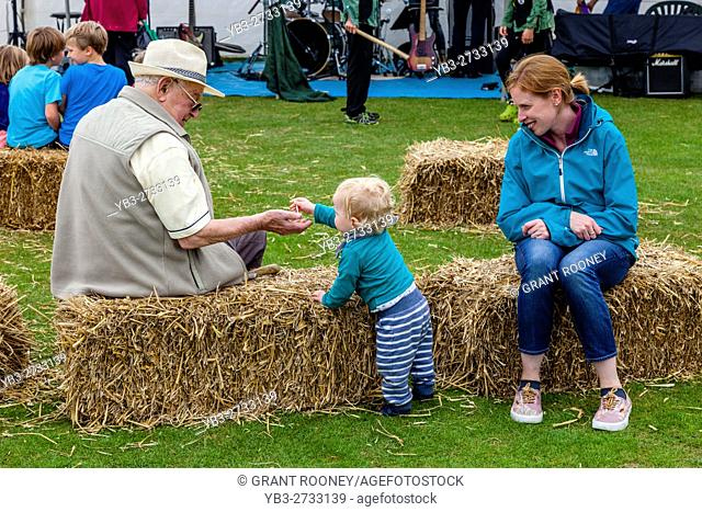 A Small Child Interacting With A Senior Man At The Annual Hartfield Village Fete, Hartfield, East Sussex, UK