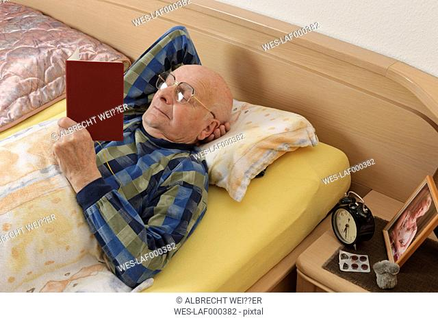 Old man reading in bed