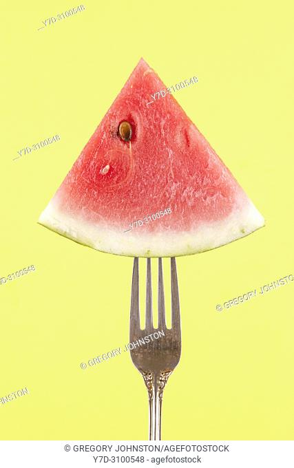 A concept image of a slice of watermelon on a fork against a yellow background