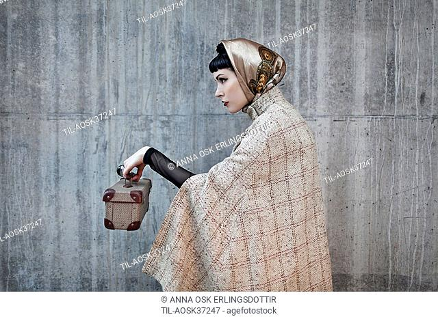 Female wearing headscarf wearing tweed cape holding a small case in profile