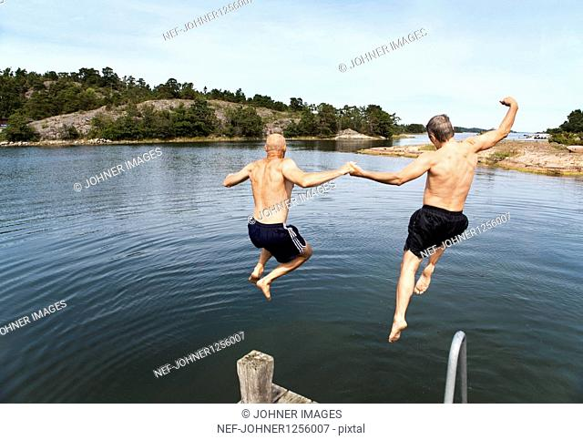 Two men jumping into sea