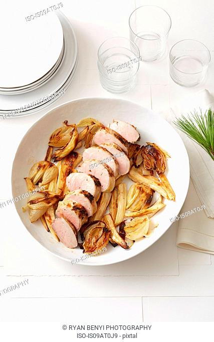 Still life of Pine-Roasted Pork Tenderloin with Parsnips and Onions
