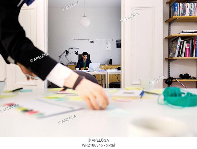 Cropped image of businessman's hand holding reminder notes while colleague working in background