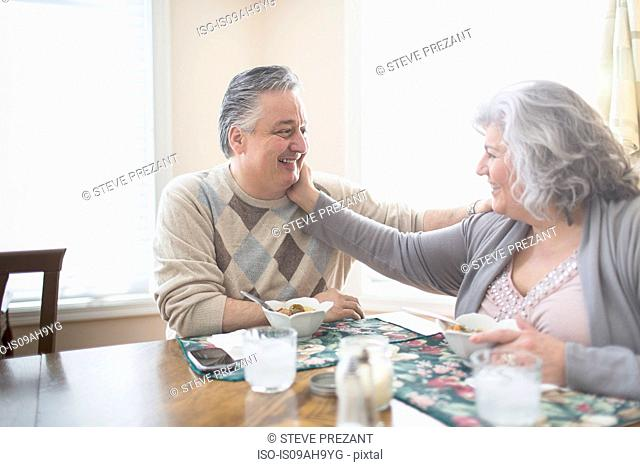 Affectionate mature adult couple having lunch at home