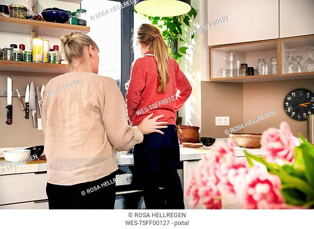 Back view of mother and daughter cooking together in the kitchen