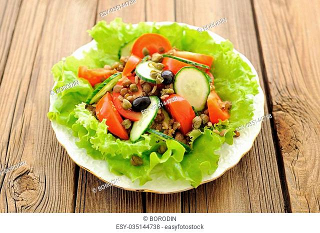 Lentil salad with fresh tomatoes, cucumbers, capers and lettuce on wooden table horizontal